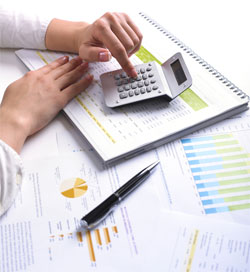 A photograph showing a hand surrounded by a calculator and numerous documents with charts and data. This photo represents the higher education strategic enrollment planning process where institutional leaders must use data to guide their future enrollment goals and processes.