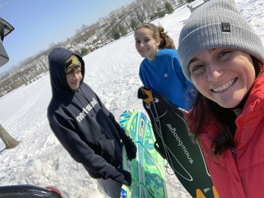 Amy Weiss of RNL and her two children on a mountain skiing.
